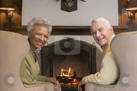 Couple sitting in living room by fireplace smiling stock photo,  by Monkey Business Images