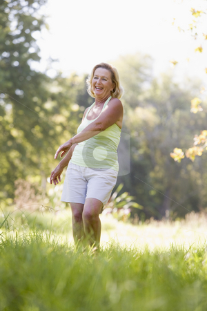 Woman walking outdoors smiling stock photo,  by Monkey Business Images