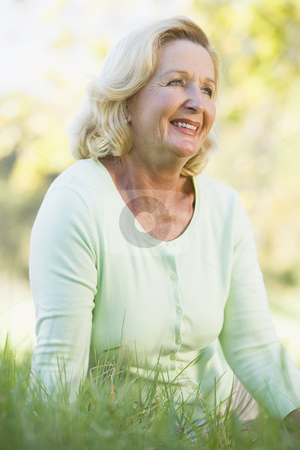Woman sitting outdoors smiling stock photo,  by Monkey Business Images