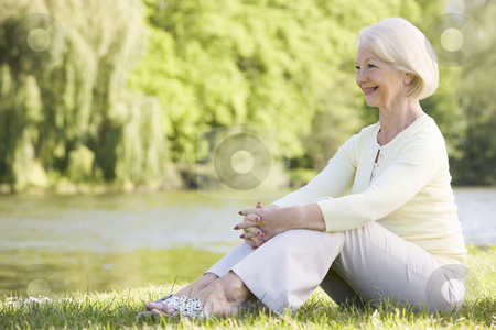 Woman outdoors at park by lake smiling stock photo,  by Monkey Business Images