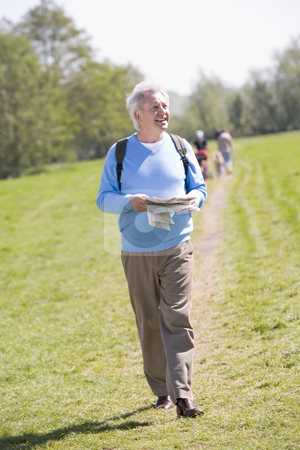 Man walking outdoors holding map smiling with people in backgrou stock photo,  by Monkey Business Images