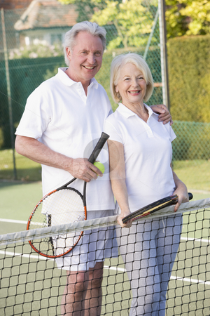 Couple playing tennis and smiling stock photo,  by Monkey Business Images