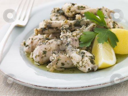 Frogs Legs Fried in Garlic and Herb Butter with Lemon stock photo,  by Monkey Business Images