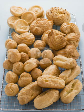 Selection of Choux Pastry Buns on a Cooling Rack stock photo,  by Monkey Business Images