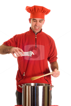 Adding Spices stock photo, A chef wearing red is adding some salt to his pot of soup, isolated against a white background by Richard Nelson
