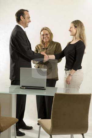 People in Business Meeting - Vertical stock photo, Three people are in a business meeting.  They are smiling at each other and shaking hands.  Vertically framed shot. by Orange Line Media
