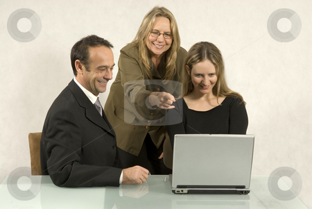 People in Business Meeting - Horizontal stock photo, Three people are in a business meeting.  They are smiling and looking at the screen of the laptop.  Horizontally framed shot. by Orange Line Media