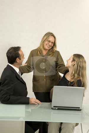 People in Business Meeting - Vertical stock photo, Three people are in a business meeting.  They are smiling and looking at each other.  There is a laptop on the table.  Vertically framed shot. by Orange Line Media