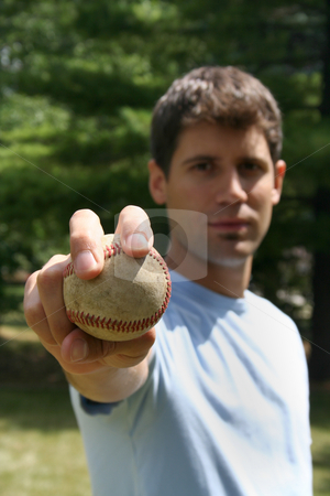 Man with Baseball - Vertical stock photo, A man holding a baseball with an outstretched hand.  He is gazing at the camera.  Vertically framed shot. by Orange Line Media
