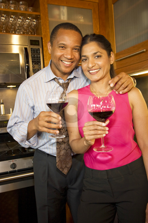 Couple with Wine - Vertical stock photo, Couple standing in kitchen smiling, laughing and holding wine glasses. Vertically framed photo. by Orange Line Media