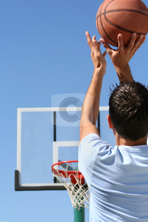 Boy with Hoop - Vertical stock photo, The rear view of a young boy shooting a basketball toward a hoop. Vertically framed shot. by Orange Line Media
