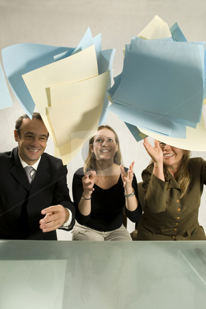 Paperwork in the Air - Vertical stock photo, A man and two women throwing paperwork in the air.  They are wearing office attire and are smiling. Vertically framed shot. by Orange Line Media