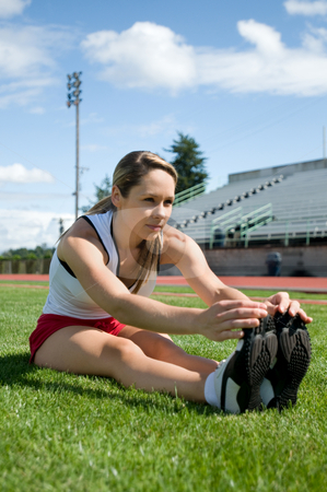 Woman Stretching - Vertical stock photo, Young woman stretching in the grass at a track. Vertically framed photo. by Orange Line Media