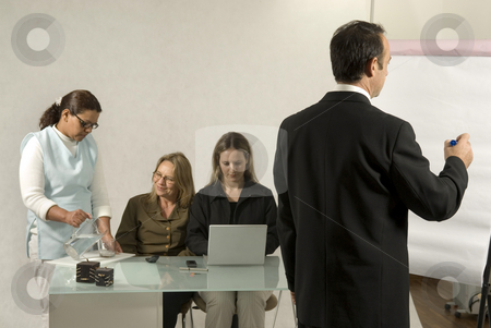 Office Team - Horizontal stock photo, A man and three women in an office setting.  The man is drawing on a drawing board, and the women are working behind a desk. Horizontally framed shot. by Orange Line Media