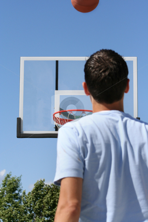 Boy with Hoop - Horizontal stock photo, The rear view of a young boy facing a hoop as a basketball ascends toward it. Horizontally framed shot. by Orange Line Media