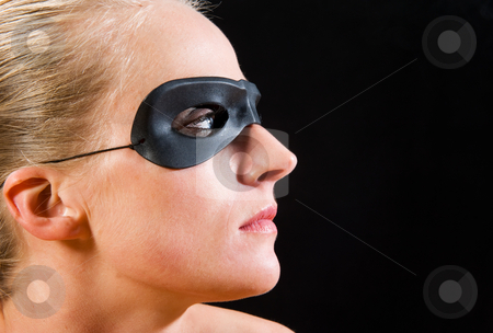 Blond girl portrait stock photo, Blond girl wearing a mask, seen in profile against black background by Flemming Jacobsen