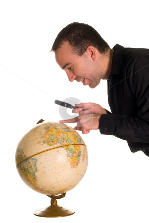 Man Looking At Globe stock photo, A man using a magnifying glass to look at a globe of the planet by Richard Nelson