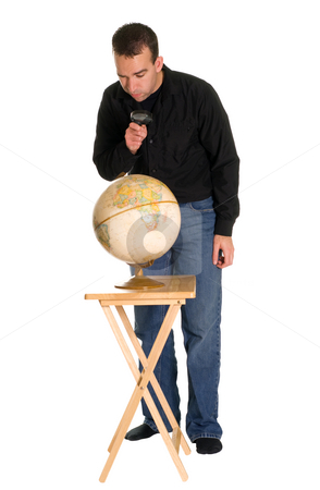 Man Examining The Globe stock photo, Full body view of a man using a magnifying glass to examine a model of the earth by Richard Nelson