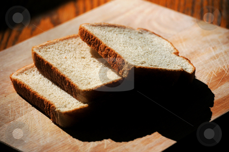 Bread on a cutting board stock photo, Slices of bread on a cutting board by Tim Markley