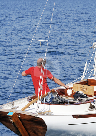 Man on a sailboat stock photo, Sailor pulling rope on a boat in navigation by Massimiliano Leban