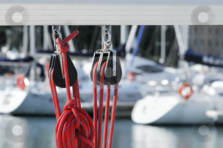 Sailing pulleys with rope stock photo, Close-up of sailing pulleys with red rope on a boom with boats of a marina in background by Massimiliano Leban
