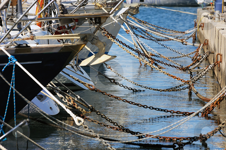 Moored boats stock photo, Detail of ropes and chains securing boat to pier in a marina by Massimiliano Leban