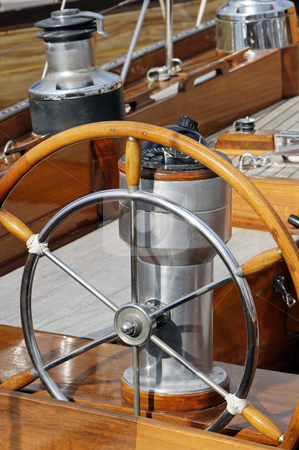 Wooden boat stock photo, Detail of an old-fashioned boat deck with rudder, compass and other navigation tools by Massimiliano Leban