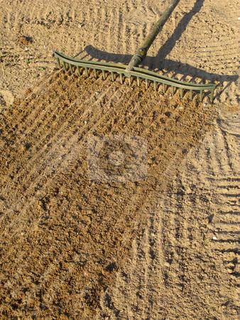 Raking sand with a bunker trap rake. stock photo, Raking sand with a bunker trap rake. by Stephen Rees