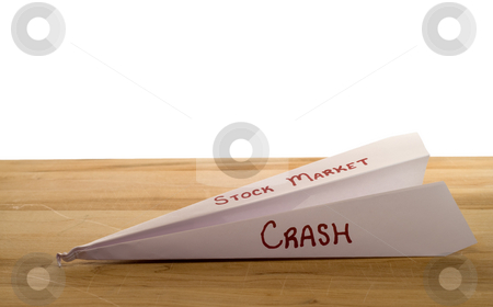 Stock Market Crash stock photo, A crumpled paper plane crashed on a wooden board, symbolizing a crash of the stock market by Richard Nelson
