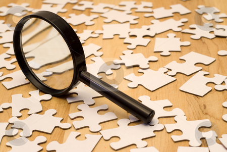Piece Of The Puzzle stock photo, Magnifying glass looking for a piece of the puzzle by Richard Nelson