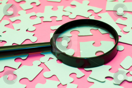 Searching For The Right Piece stock photo, Black magnifying glass searching for the right piece of the puzzle by Richard Nelson