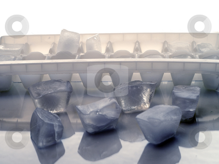 Ice Cube Tray stock photo, An ice cube tray with loose ice cubes on a reflective surface by Richard Nelson