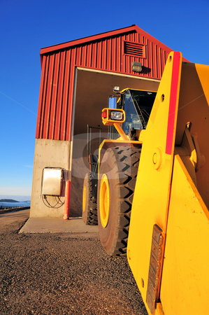 Traktor And Building stock photo, Large front loading traktor and salt storage building againt a clear blue sky. by Lynn Bendickson