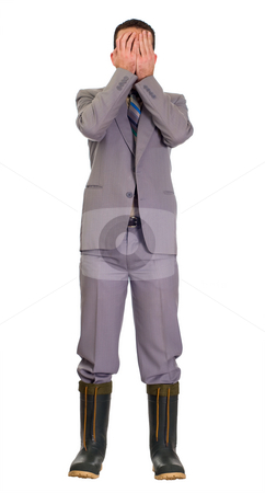 Scared Businessman stock photo, Concept image of a full body view of a businessman wearing rubber boots trying to make it in todays economy by Richard Nelson