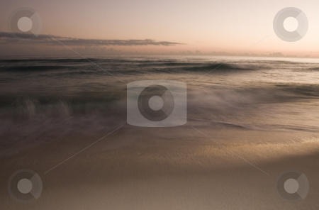 Fuzzy Beach stock photo, A long exposure of the surf rolling onto the beach at sunset by A Cotton Photo