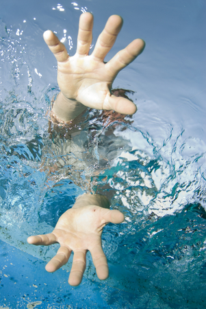 Reach stock photo, Underwater view of a sailor reaching into the water by A Cotton Photo