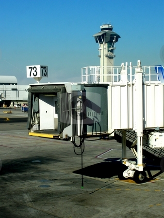 Jetway stock photo, Jetway at an airport with control tower in the background. by Henrik Lehnerer