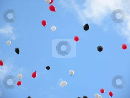Soaring balloons stock photo, Red, white, and black balloons soaring in the sky by Rob Wright
