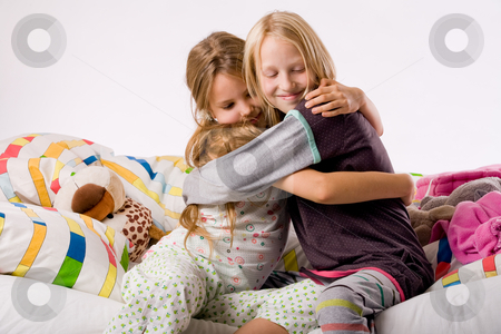 Hugging sisters stock photo, Two young children enjoying their colorful bed by Frenk and Danielle Kaufmann