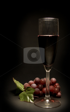 Glass of Red Wine stock photo, A glass of red wine and a bunch of grapes. by Robert Byron