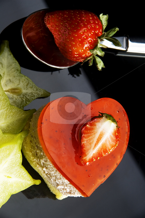 Heart cake stock photo, Heart shaped strawberry cake with carambola or star fruit decoration over black background by Francesco Perre