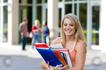 Student Holding Books - Horizontal stock photo, Young smiling female student carrying her books outside of school.  There are kids in the background. Horizontally framed photo. by Orange Line Media