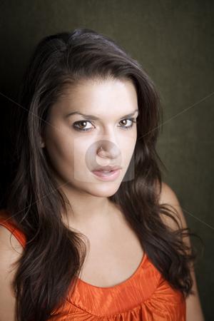 Pretty Hispanic Woman stock photo, Pretty Hispanic woman in orange on green background by Scott Griessel