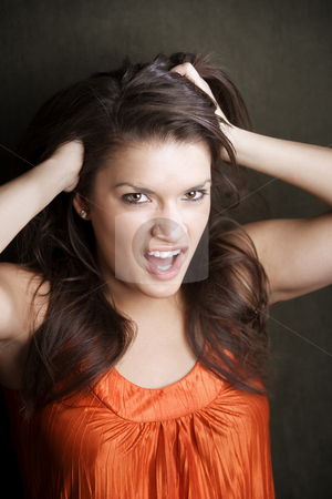 Frustrated Hispanic Woman stock photo, Frustrated Hispanic woman in orange on green background by Scott Griessel