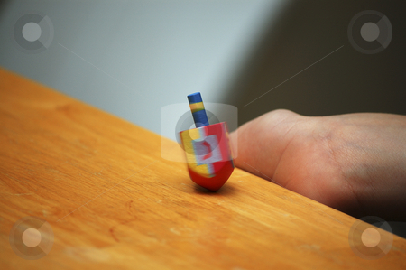 Child spinning a dreidel during Hanukkah stock photo,  by Heather Shelley