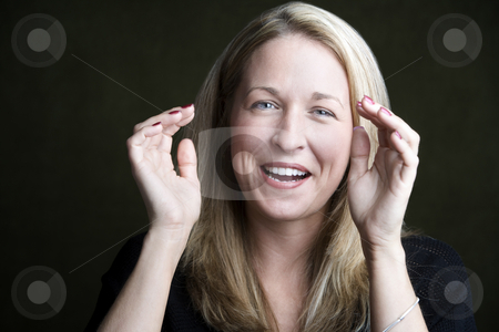 Pretty Blonde Woman Laughing stock photo, Portrait of pretty blonde laughing woman on a dark background by Scott Griessel