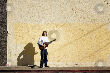 Young street musician stock photo, Young man on street with guitar and hat by Scott Griessel