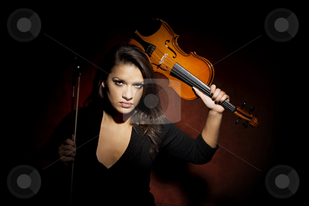 Hispanic woman holding violin as a weapon stock photo, Pretty Hispanic woman in studio with violin raised above her head by Scott Griessel