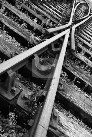 Directionless stock photo, An oblique black and white shot of railway track, showing a converging and diverging set of tracks with the points in the middle. by Tim Green