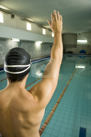 Swimmer with Hand in Air - Vertical stock photo, Swimmer standing by a pool with a cap on holding his hand in the air. Vertically framed photo. by Orange Line Media